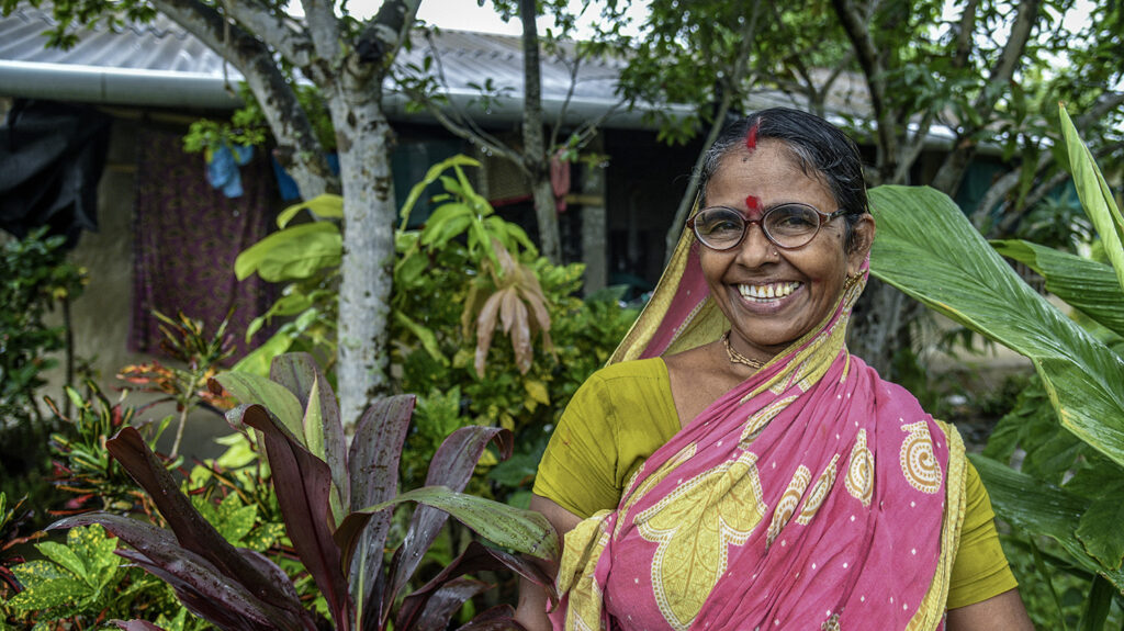 A woman wearing a pink sari is standing in her garden. She is smiling and wearing glasses.