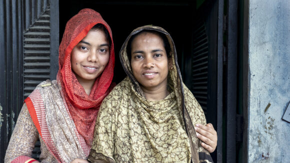 in Bangladesh, two women stand with their arms round each other outside their home.