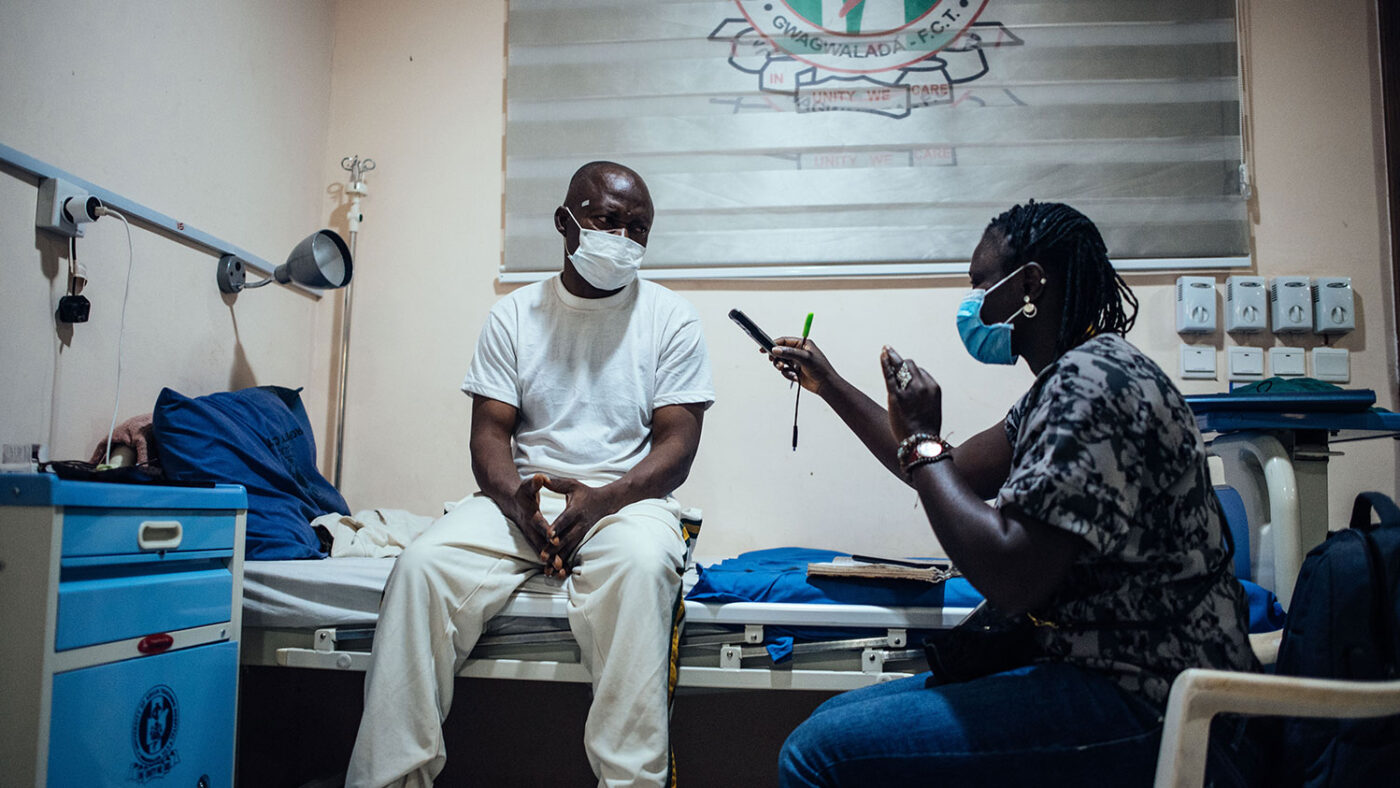 A man sitting on a hospital bed is interviewed by a Sightsavers staff member.