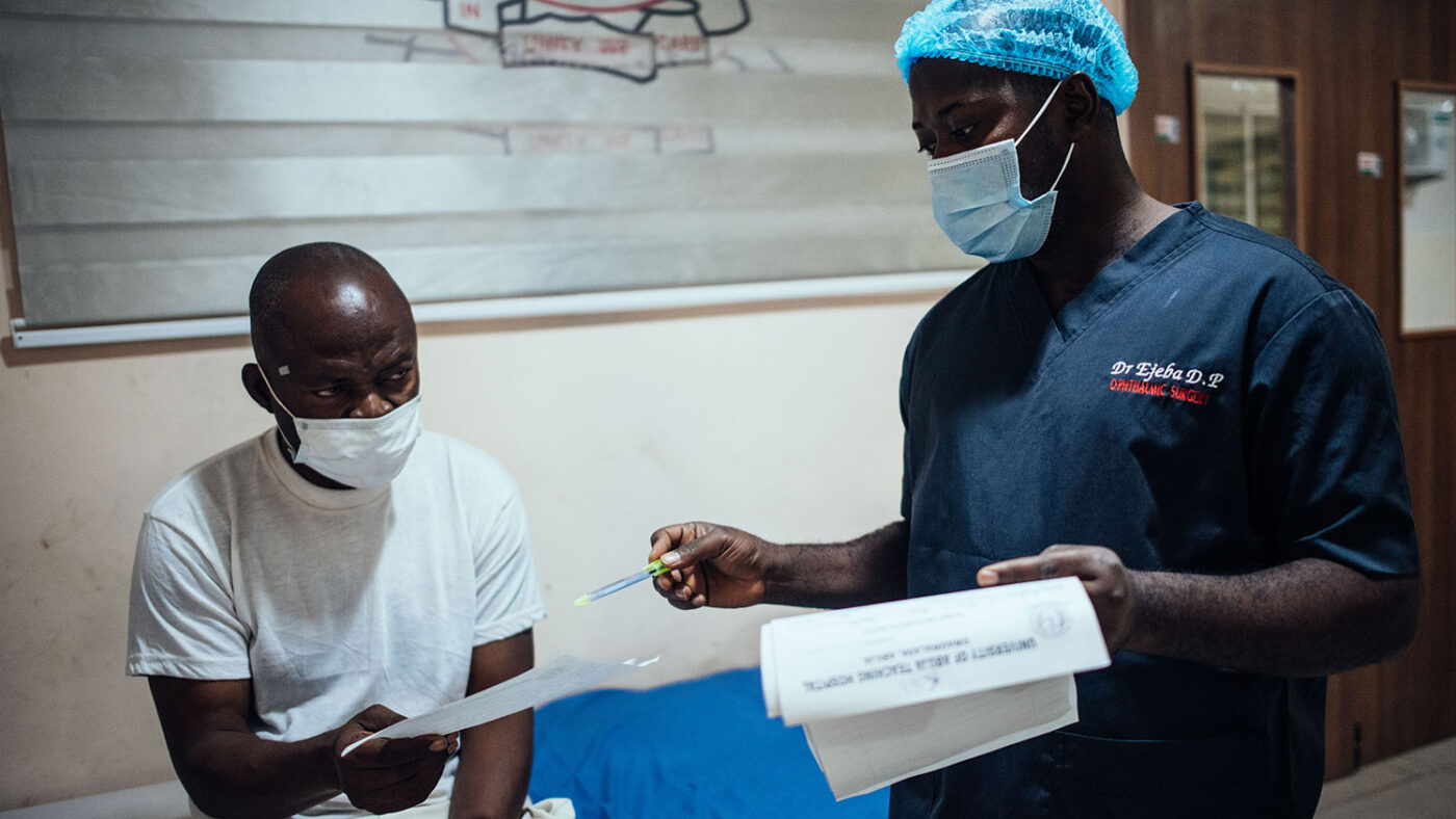 A man speaks to a health care worker in a hospital.