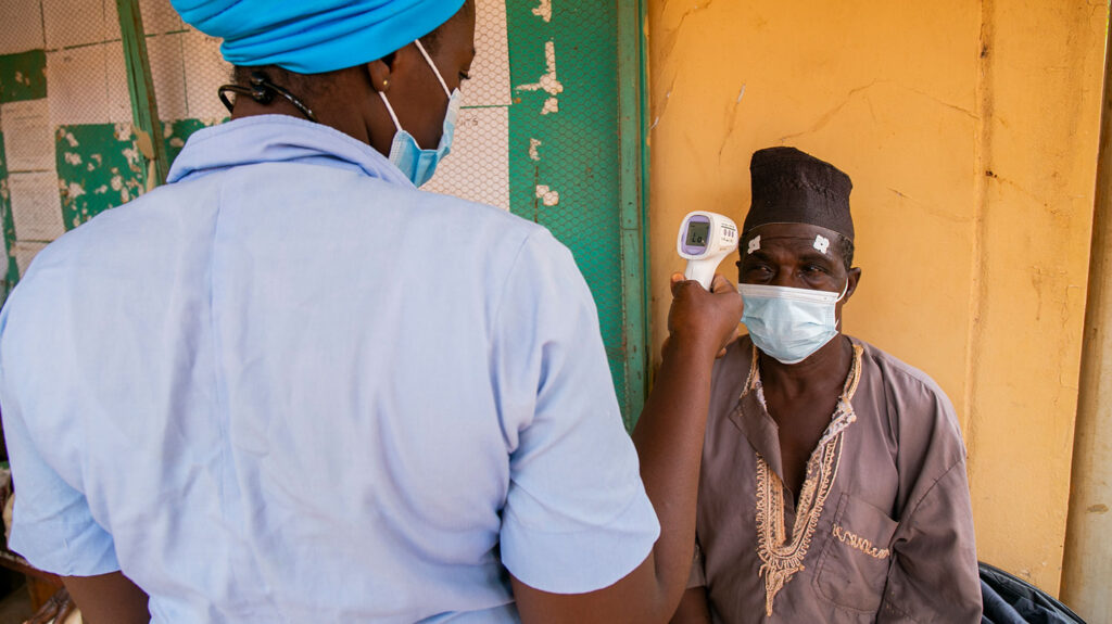 A man wearing a face mask has his temperature taken by a health worker.