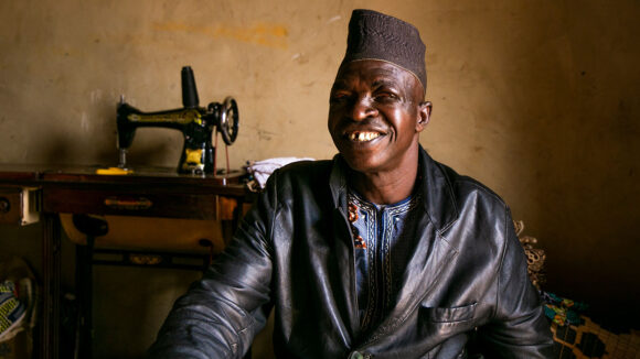 A man sitting in front of a sewing machine smiles at the camera.