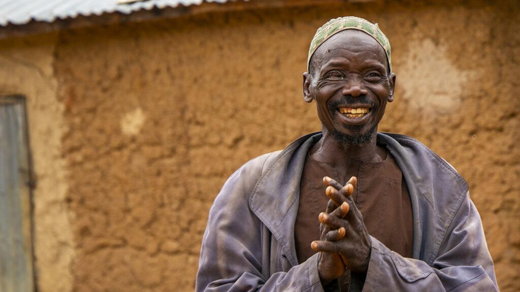 Adou smiles outside his home.