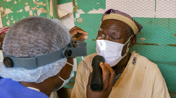 Sina wears a mask while an eye health worker shines a torch into his eyes to check for trachoma.