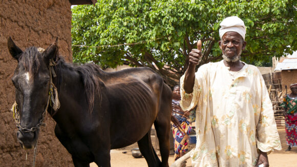 Sonbobia stands outside his home with his horse. He holds up his thumb and smiles at the camera.