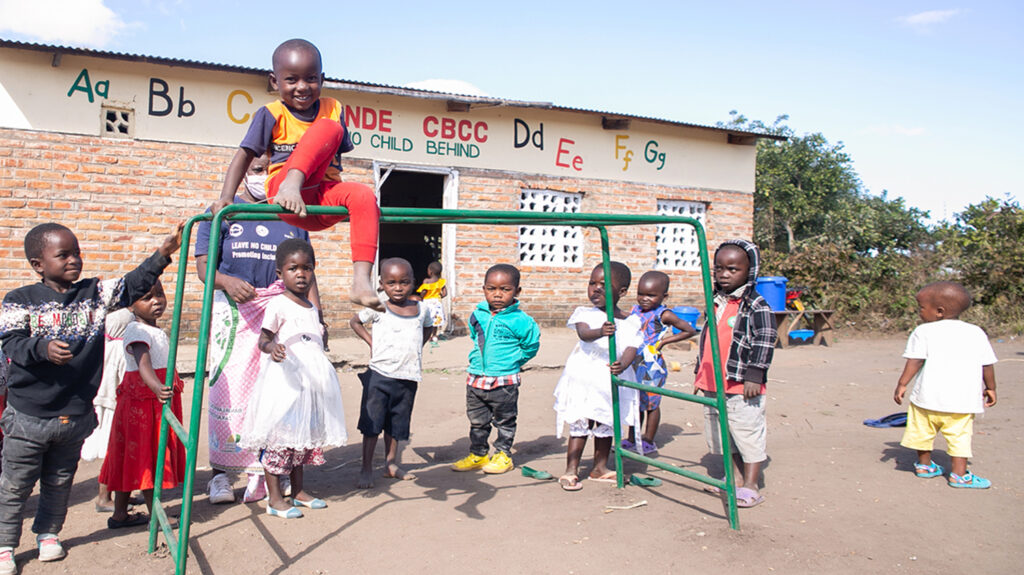 A group of young children playing on a climbing frame outside a school