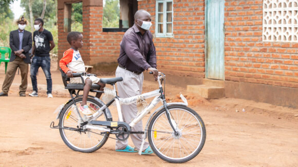 A man pushing an adapted bicycle with a child sitting on a seat at the back