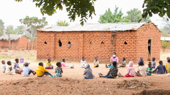 Young children sitting in a circle outside being taught vowels by their caregiver