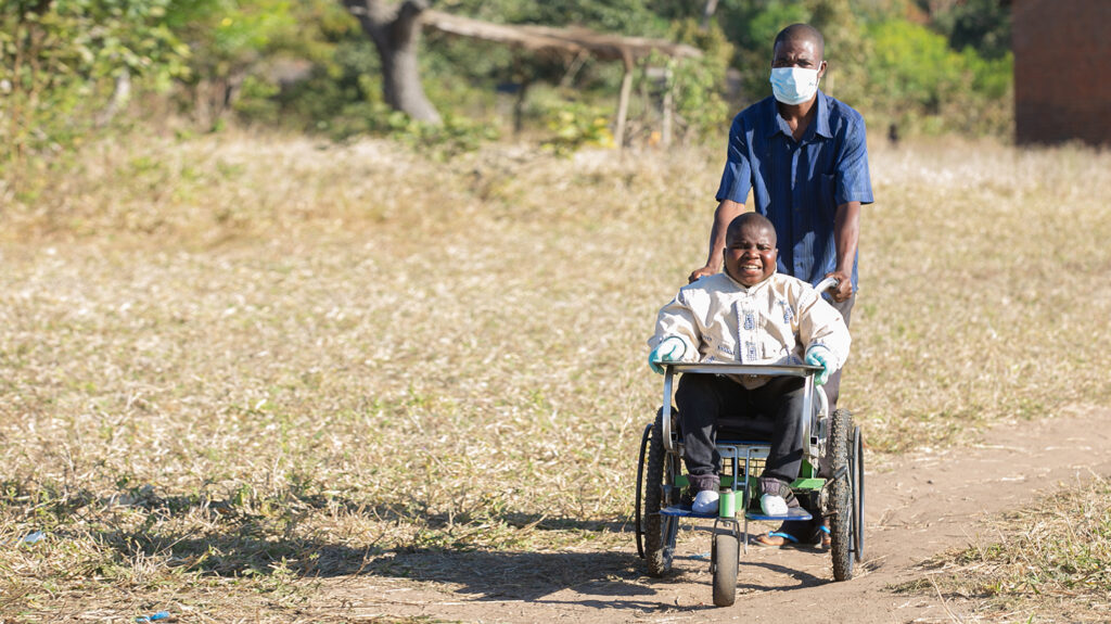Chikumbutso Diverson escorting his son, Enock, to school in an adapted wheelchair.