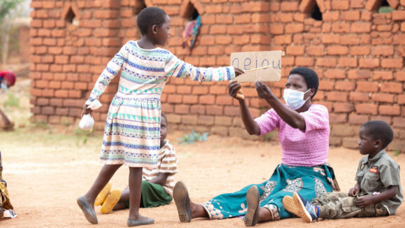 Girl pointing to the letter U at an outdoor school with other children