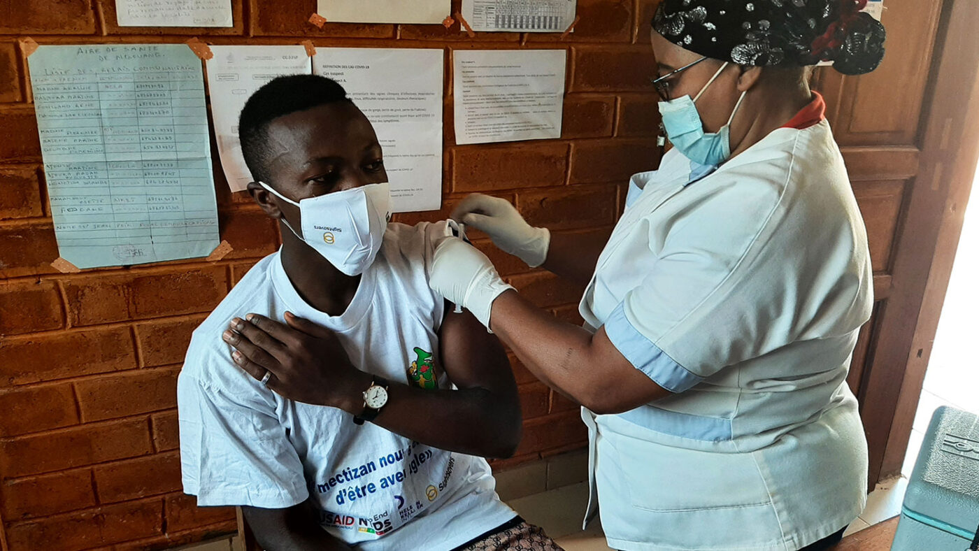 A man is given the COVID-19 vaccine by a health care worker.