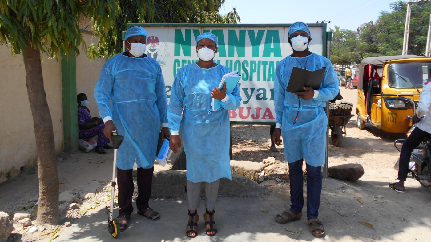 Three people in protective clothing and masks stand outside conducting Covid research.