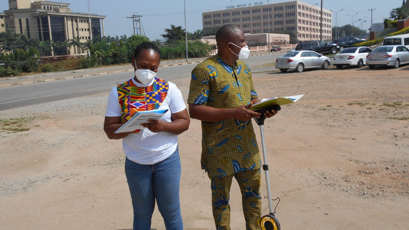 Two researchers are standing outside conducting an audit.
