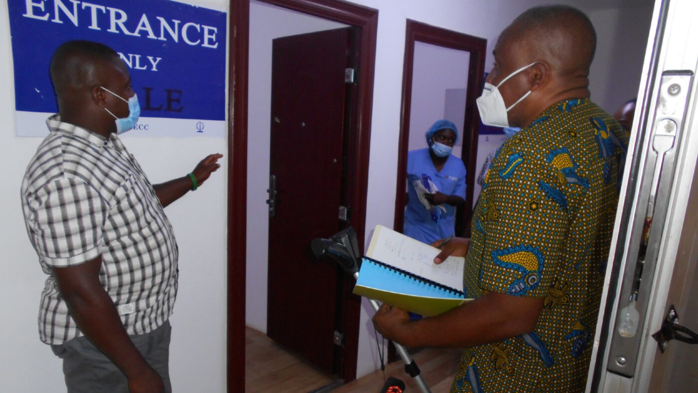 Two men in masks are inside a treatment facility conducting an audit.