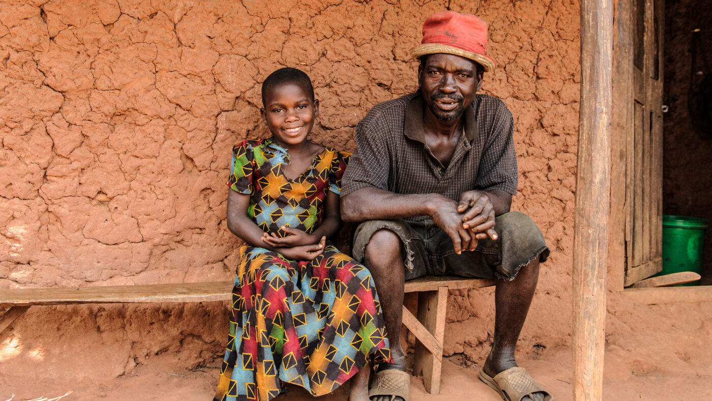 A young girl sits outside smiling on a bench wearing a colourful dress next to her father.