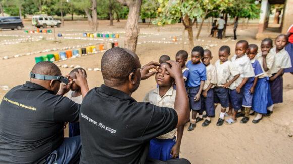 A queue of school children in uniform line up to receive an eye examination.