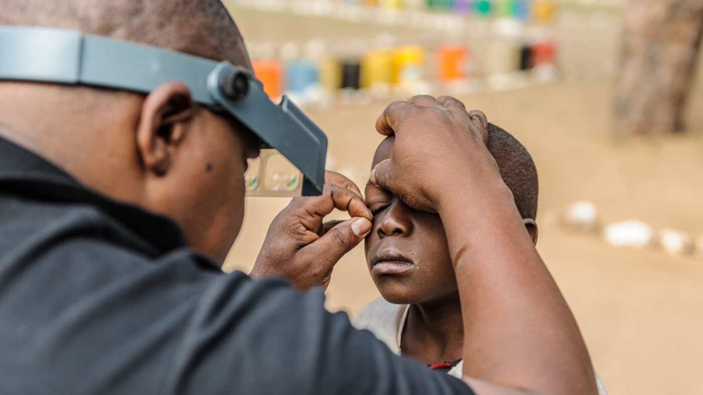 A young child has their eye held open during an eye examination.