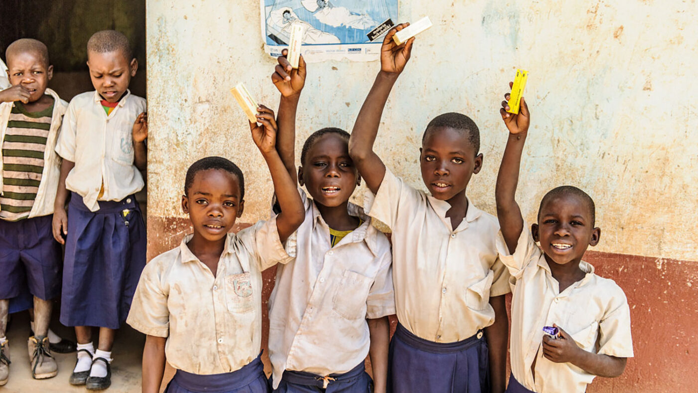 A group of young children in uniform smile and hold up their treatment following an eye health screening.