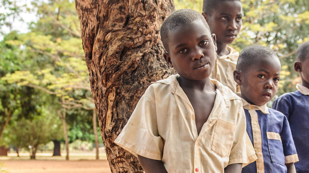 A young girl in school uniform stands outside in front of a tree and some classmates.
