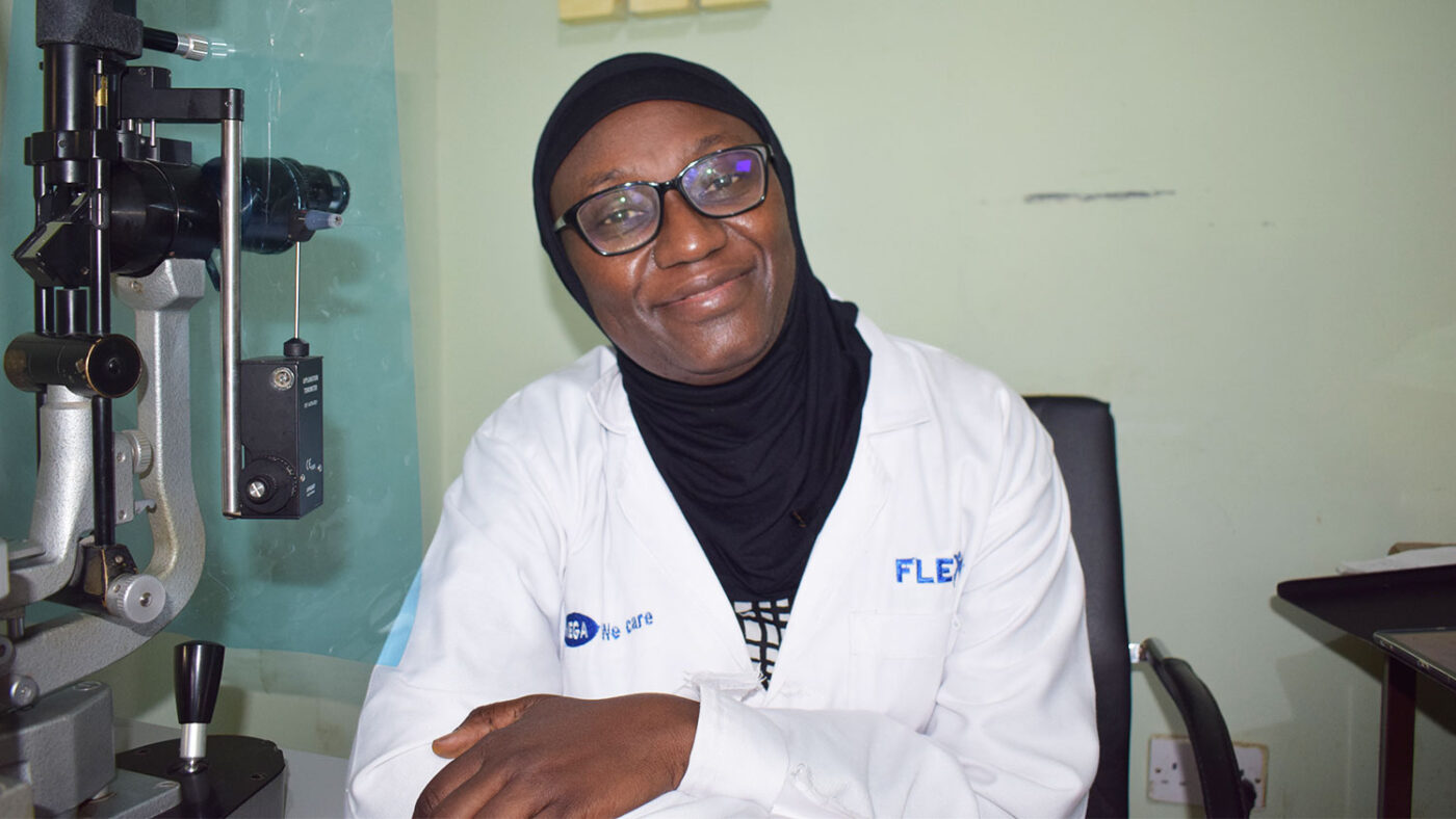 A doctor smiles at the camera in her office.