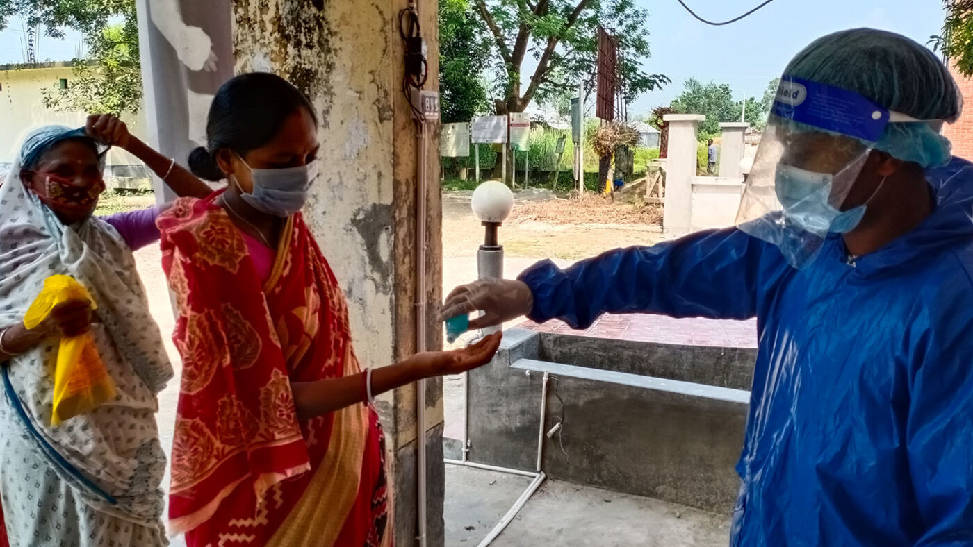A woman holds her hand out while a health worker squirts hand sanitiser into it.
