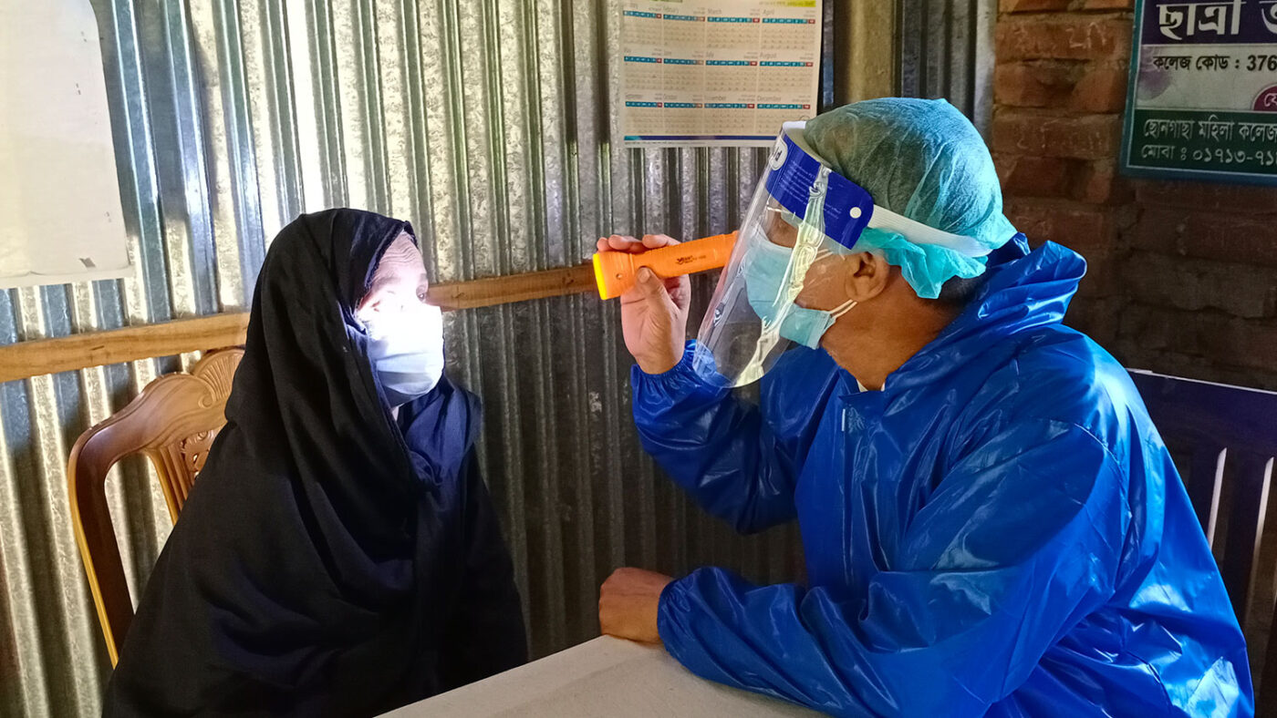 A woman's eyes are examined by a health worker wearing PPE.