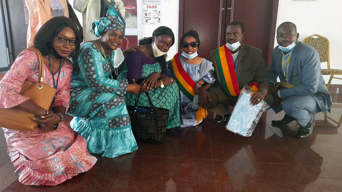 Five people, including the President of the Association des People of Small Size and the President of the Malian Union of the Blind, smile at the camera.
