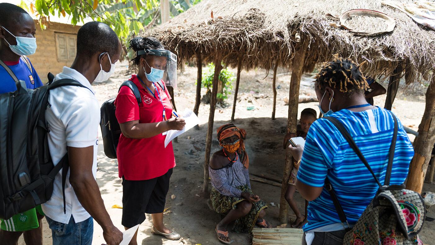 Three eye health workers wearing masks speak to local villagers.