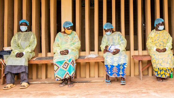 Four patients wait while socially distancing for their trauchoma surgery while wearing PPE and face masks.
