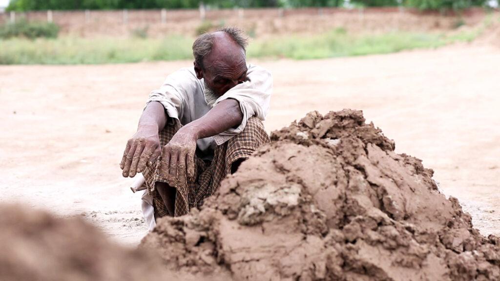 A man rubs his eyes on his upper arm while making bricks.