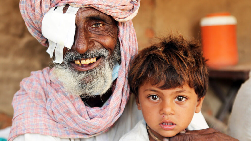 A man with a bandage over his right eye smiles for a photo with his young grandson.