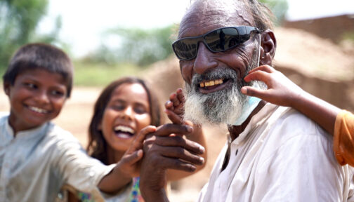 A man wearing sunglasses smiles with his two happy grandchildren.
