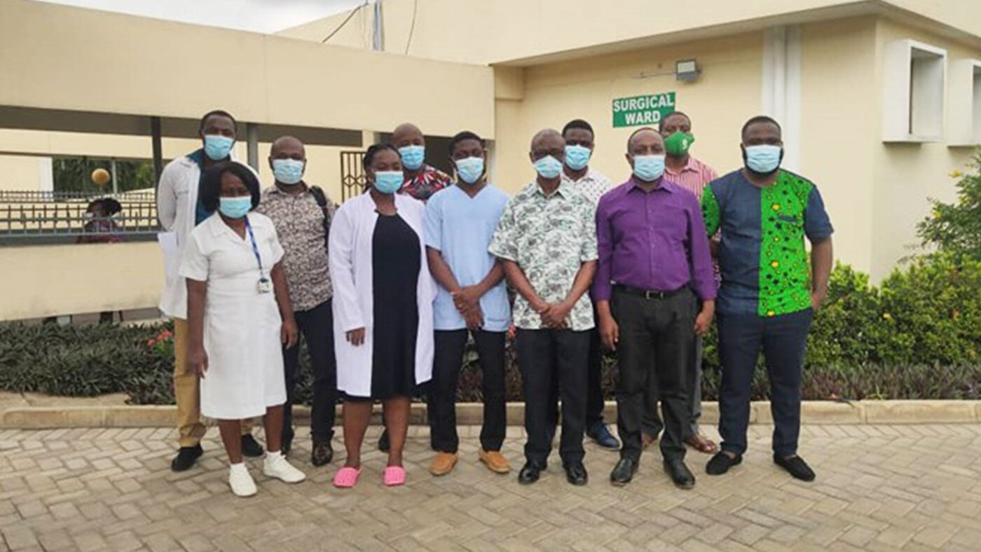 A group of health workers wearing surgical masks pose for a photograph in front of a hospital.